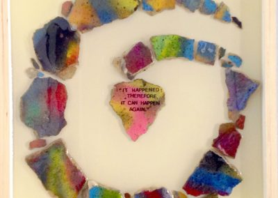 The Evolution of Mankind, by Julie Weaverling, rocks from the Berlin Wall, text, resin, 20 x 20